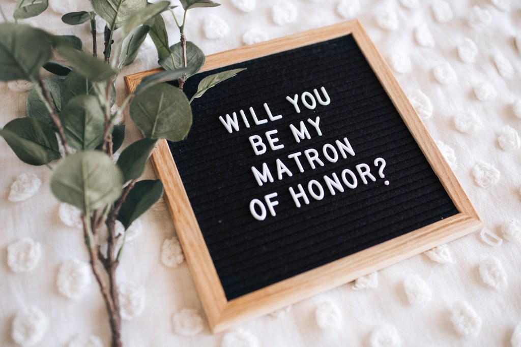 """will you be my matron of honor?"" written out on a letterboard"