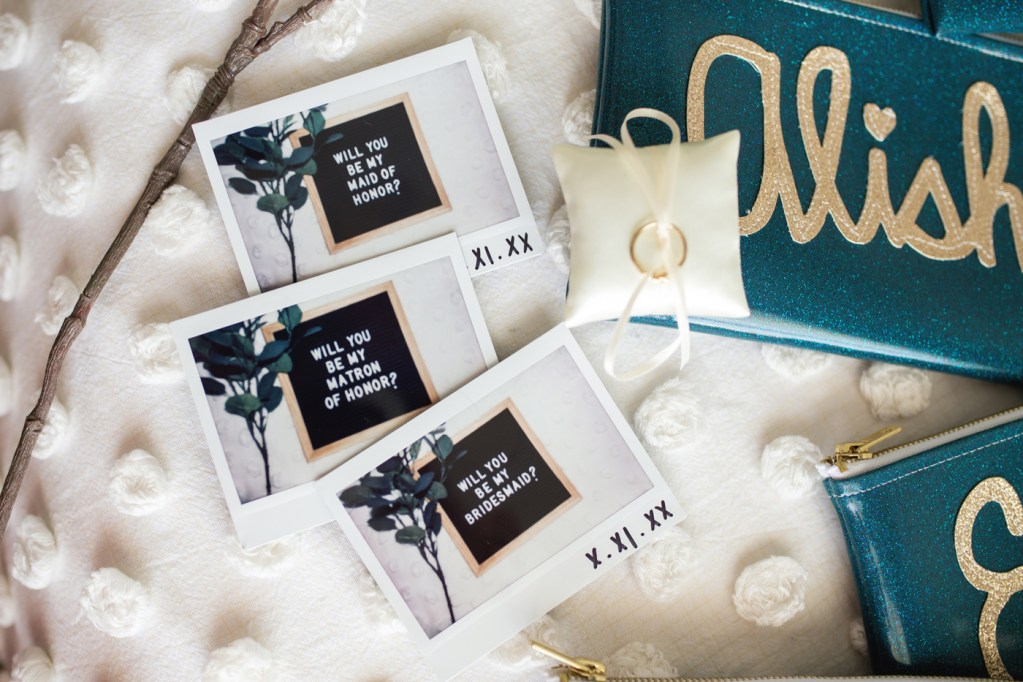 bridesmaids proposal polaroids laid out with knot ring