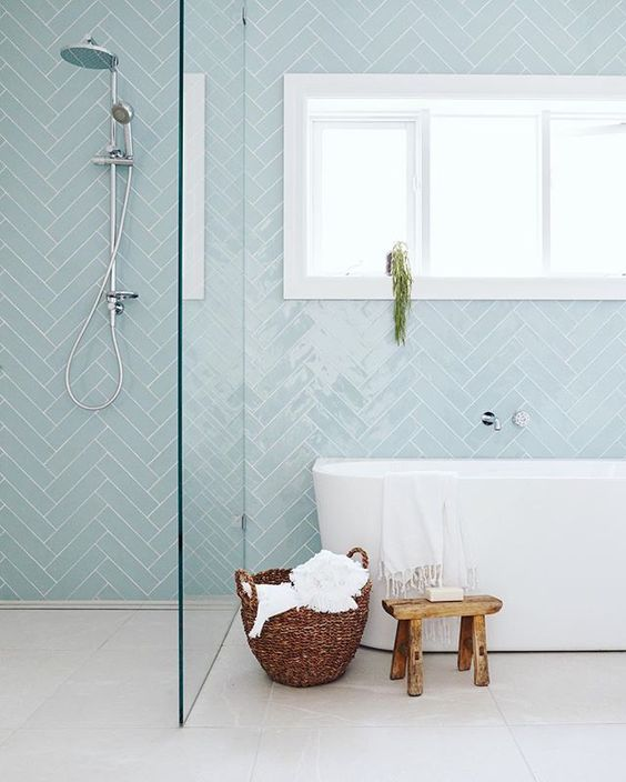 baby blue herringbone tiled bathroom with freestanding tub