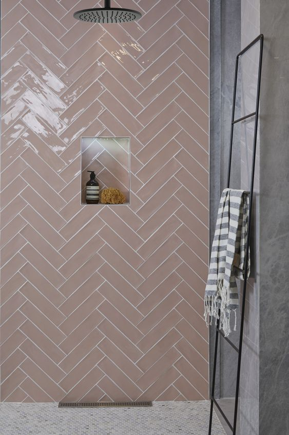blush herringbone tile shower with niche