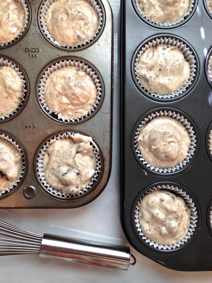 Muffin tins filled with cupcake batter, ready for the oven