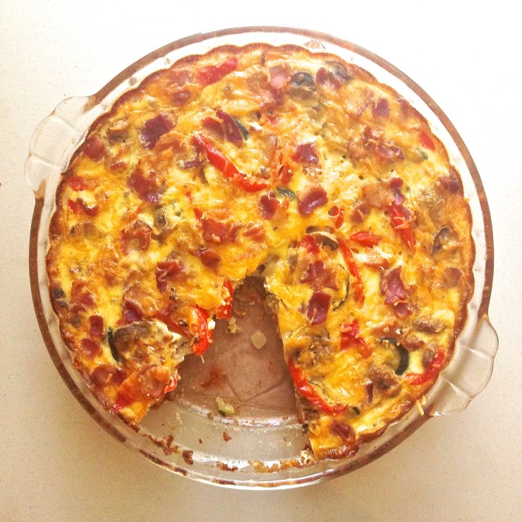 cheesy bacon and veggie quiche - baked with a slice missing