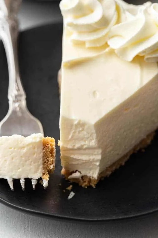 Slice Of No Bake Cheesecake On A White Plate With Fork Taking Bite Out