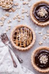 These Chocolate Peanut Butter Caramel Tarts have a crunchy shortbread crust that's filled with a creamy peanut butter date caramel and topped with creamy chocolate ganache! This decadent tart recipe is gluten-free, grain-free and vegan.