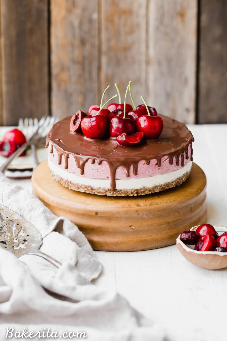 This No Bake Cherry Cheesecake has a pecan coconut crust, a layer of creamy vanilla bean cheesecake, topped by a layer of vibrant cherry cheesecake. Vegan dark chocolate ganache is spread all over the top! You'll go crazy for this gluten-free, paleo, and vegan treat.