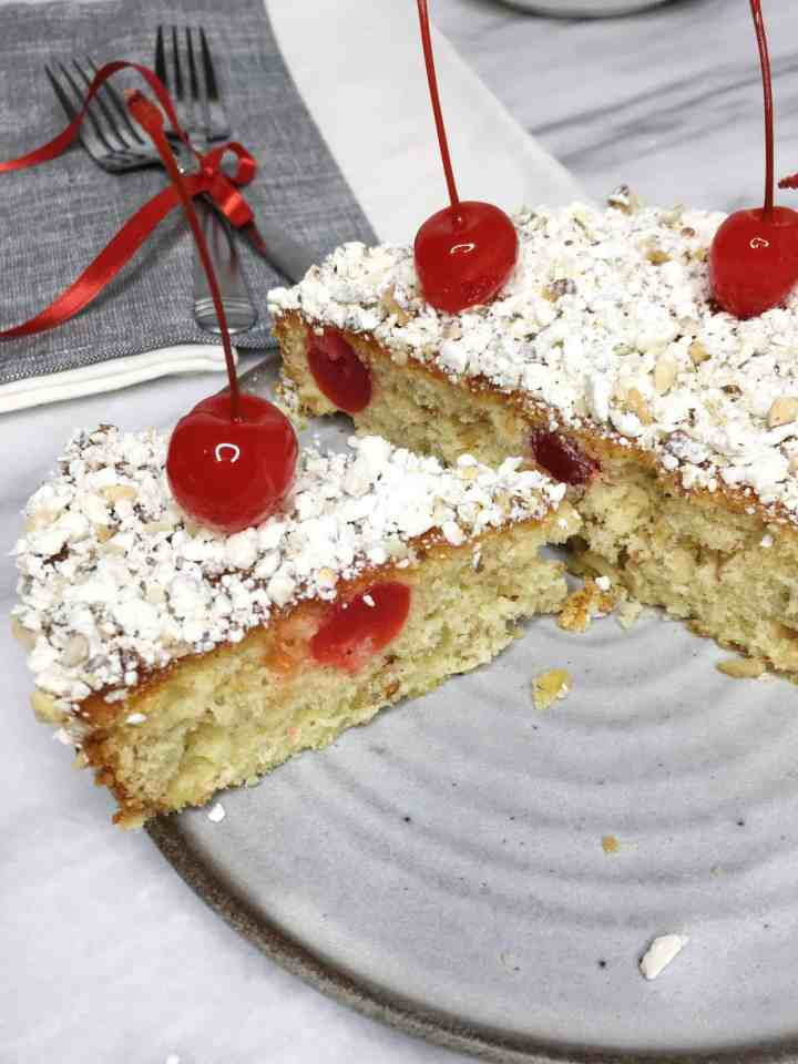 Sliced Maraschino Cherry cake on a dessert plate with flatware on background