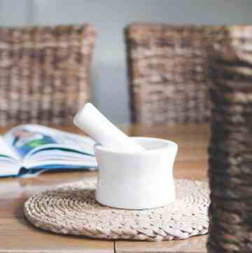 Mortar and Pestle Set on a a table with chairs around: Closeup