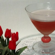 Cocktailglas met Mary Pickford cocktail met rode rozen