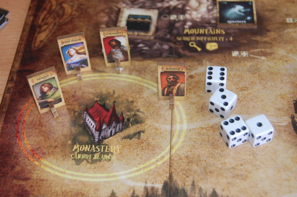 Personaggi al villaggio e i dadi. Tutti gli elementi centrali del gioco.