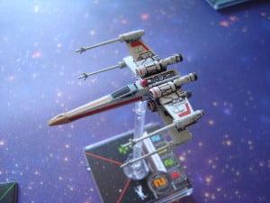 """Il nuovo X-Wing è distinguibile da quello della scatola base e della """"wave 1"""" per via della striscia gialla sul muso e del droide astromeccanico rosso."""