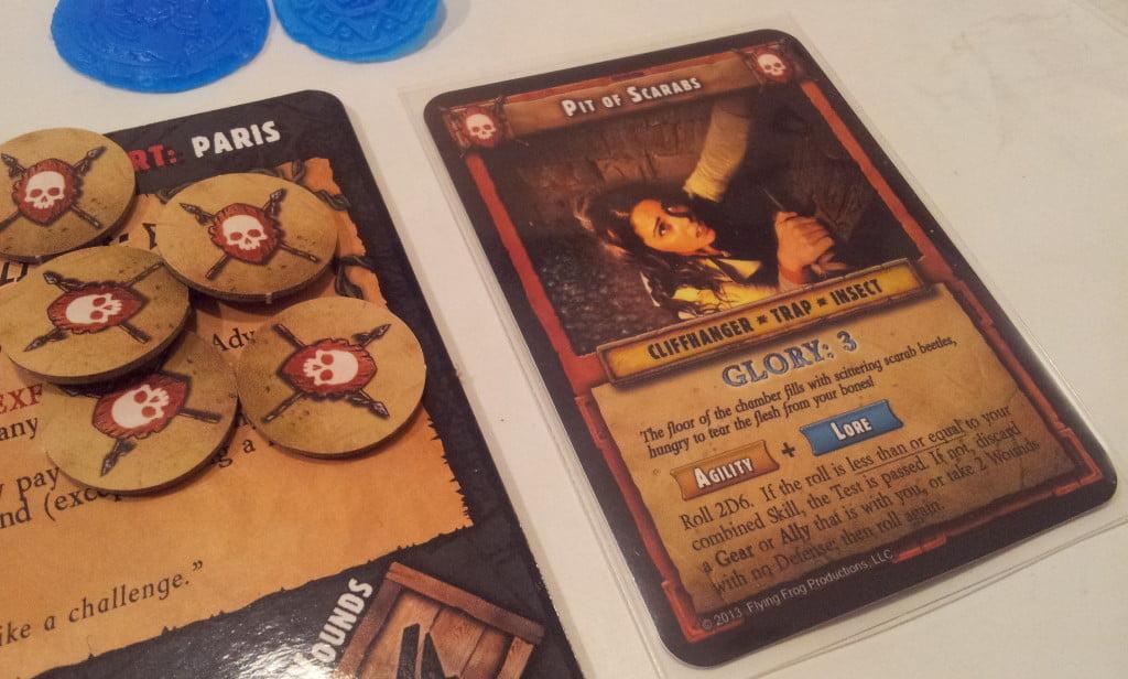 """Il cuore del gioco sono le carte Danger: questa è voltata sul lato """"Cliffhanger"""", una prova che potrebbe mettere KO il nostro personaggio. Sulla scheda giocatore a sinistra si vedono i segnalini relativi ai pericoli già superati durante la ricerca dello specifico artefatto."""