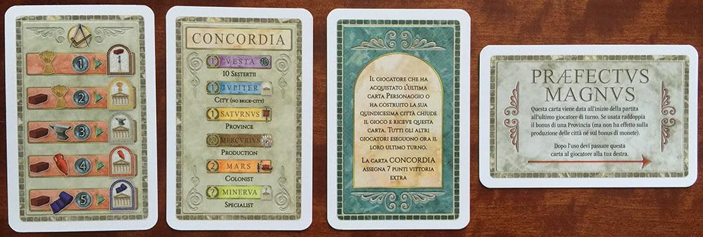 Le carte speciali: partendo da sinistra, il fronte della carta riepilogo con i costi di costruzione delle case, il retro con il promemoria del conteggio finale, la carta Concordia e il Praefectus Magnus.
