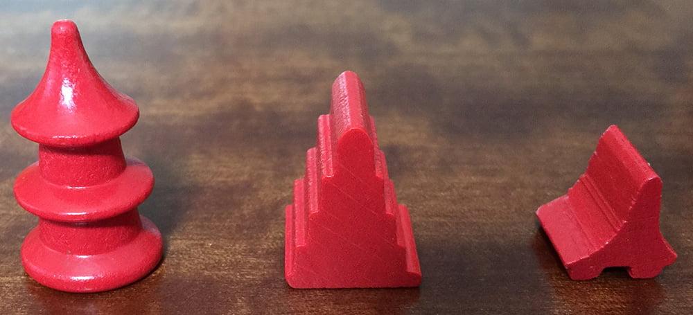 Le tre diverse tipologie di edifici a disposizione di ogni giocatore: da sinistra verso destra, la torre, il tempio e la capanna.