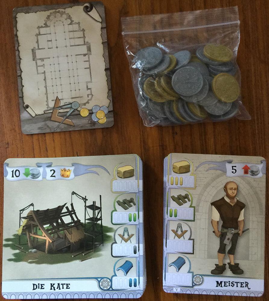 I componenti al completo: in alto vedete la carta primo giocatore e il sacchetto con le monete; in basso gli Edifici e gli Operai.