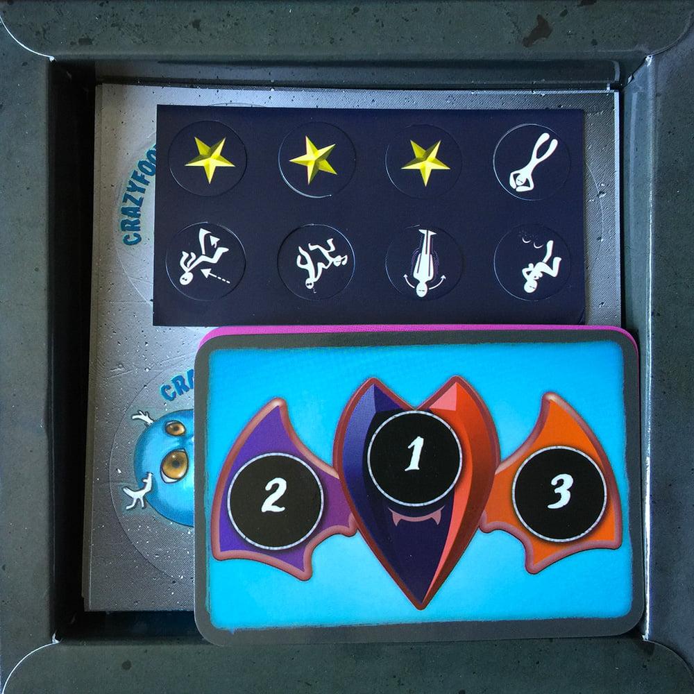 L'interno della scatola, con le carte e gli stickers del gioco.