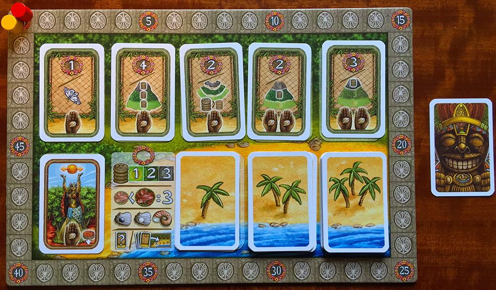 La plancia secondaria è pronta per la partita: i segnapunti sono sullo zero, i 6 bonus sono scoperti e in basso a destra vediamo i tre mazzi con le palme sul dorso. Accanto ad essa, c'è la carta del primo giocatore.