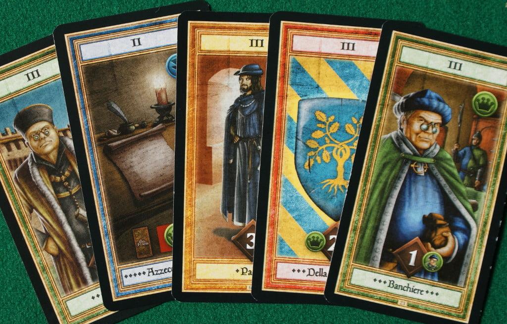 """Una """"mano"""" di carte con due personaggi standard (il primo è il banchiere e l'ultimo il Podestà), lo scudo araldico è quello della famiglia della Rovere. Infine riconosciamo Paolo e l'Azzeccagarbugli"""