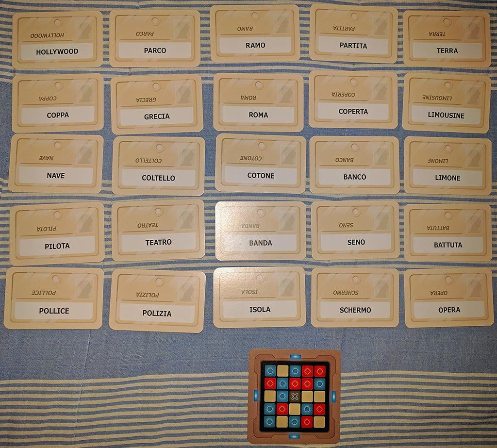 """Un esempio di griglia di gioco (notate che ogni carta """"parola"""" presenta lo stesso termine stampato sullo stesso lato in due versi differenti, in modo tale che tutti i giocatori possano visualizzare tutto senza doversi spostare."""