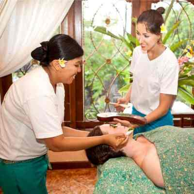5-day Traditional Balinese Facial course in Bali learn the theoretical & practical skills to give professional facials with natural ingredients. Pictured is Bali BISA trainer showing student how to apply cucumber facial.