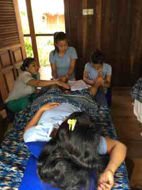 Dewi and the Siladen Resort therapies while practicing foot reflexology