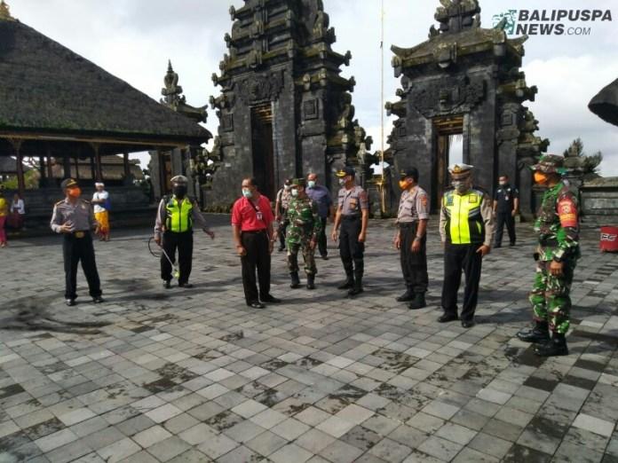 Petugas keamanan dibantu warga melakukan penyemprotan disinfektan sebelum piodalan berlangsung