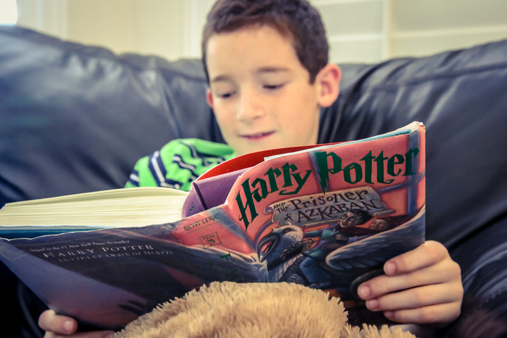 Here he is...captured again by the Harry Potter series! Just like his mom! I just wish he wanted me to read it aloud to him...