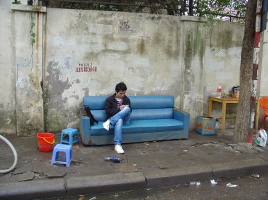 A man sitting on a couch at the street.