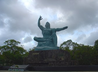 The right hand points to the sky, where the atomic bomb exploded; the left hand points towards peace.
