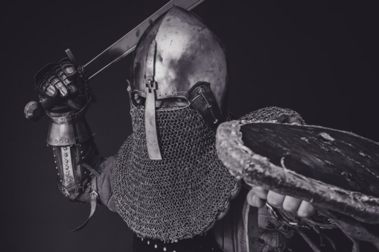 The Bomb of Galahad Satire: Image depicts a knight in full armor raising a sword.