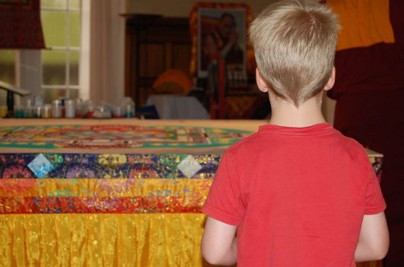 Kind vor dem Tisch mit dem Sandmandala