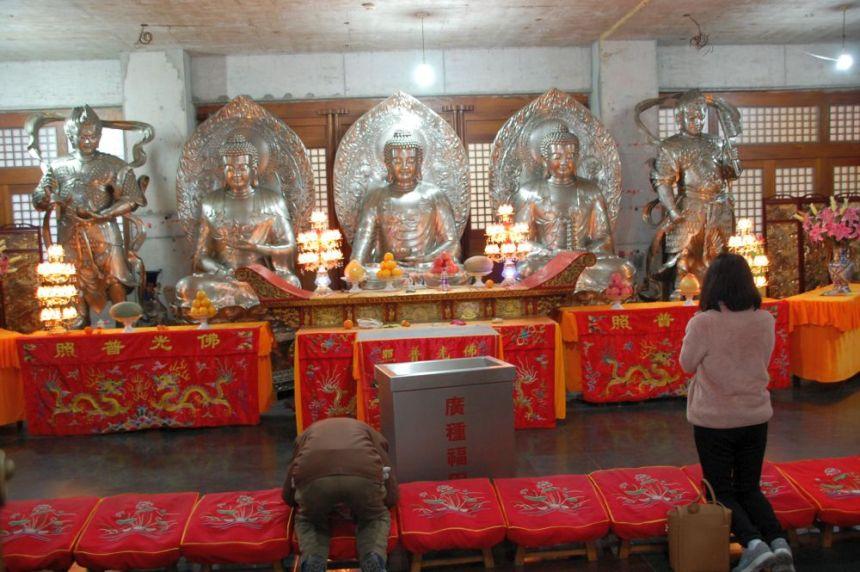 Verbeugung vor einem Buddha-Altar