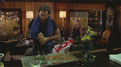 "Ty Webb's home is a marvel of subtle set design. Aside from the pile of uncashed checks, note the stake pizza and Perrier, the random sporting equipment, the wood paneling, the wilted flowers, and the ""Benihana"" decor, which Chase spontaneously damages when welcoming in his date."