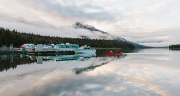 Docked charter boats at Maligne Lake, Jasper Canada. Two people canoe passed on cloudy, misty morning, admiring the Canadian Rockies.