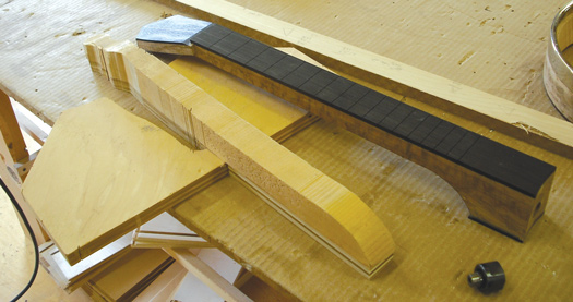 The neck blank with peghead overlay and fingerboard attached. The cradle assists in holding the neck while band sawing.