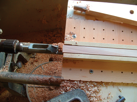 Using a tenon cutter to make the tenon on the end of the banjo's dowel stick.