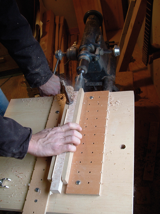 Using the jig to hold the dowel in place while the tenon is being cut.