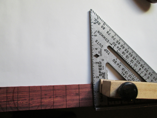 Clamping the square and fingerboard to the edge of a table keep them from moving while sawing.
