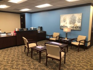 Danville, VA insurance agency office new lobby, tan and wood tone seating collection in front of wooden reception desk.