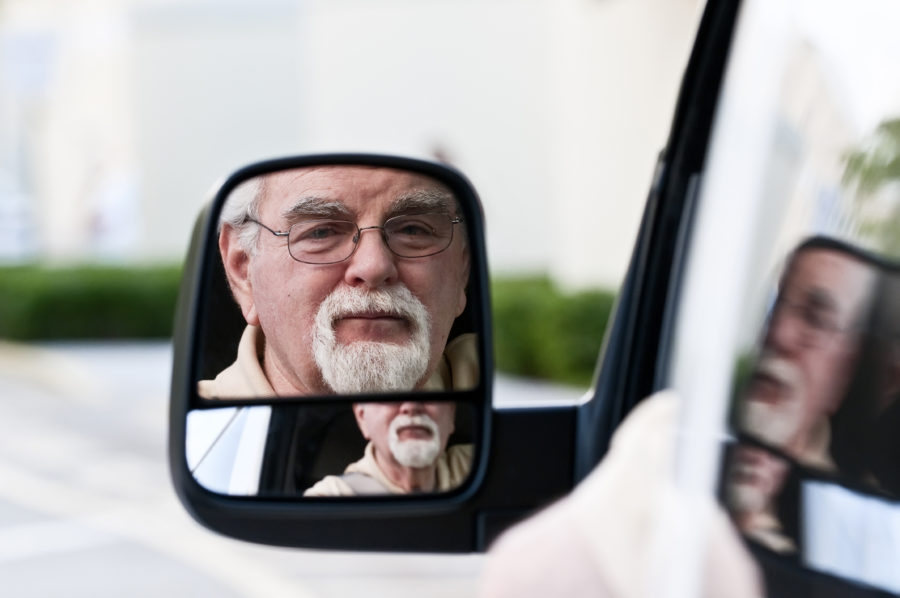 NEMT workers compensation insurance driver looking in rearview mirror