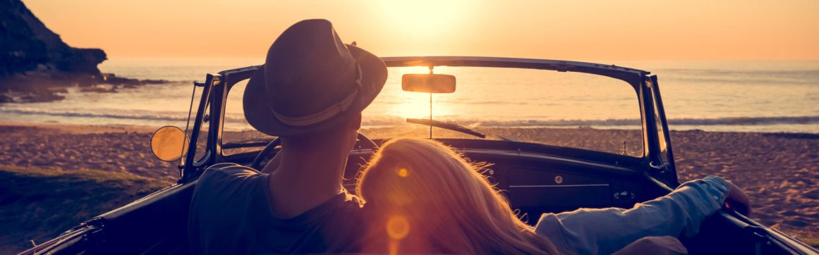 Luxury car insurance, couple watching an orange sunset over a beach in a red convertible car.