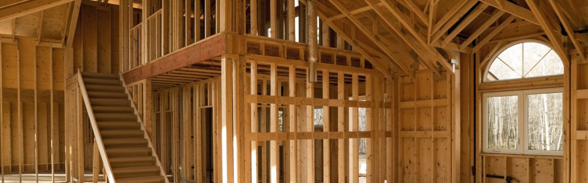 Residential framing contractor insurance, open studs and on interior of house with large vaulted ceilings under construction.