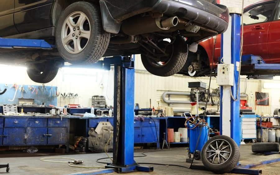 Handling common hazardous substances auto garage, two vehicles on lifts in repair shop.