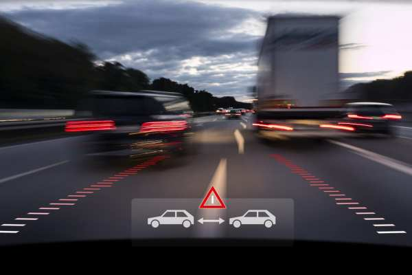 Reduce business auto livery insurance costs, windshield view of motion blur traffic with electronic technology collision avoidance warning.