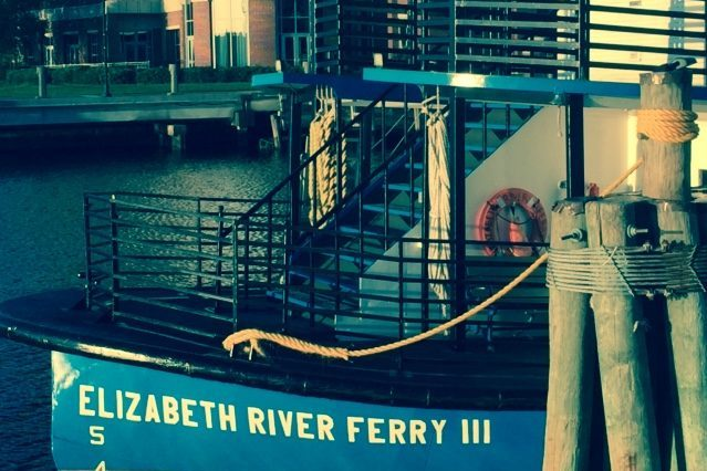 Blue bow of the Elizabeth River Ferry on water with buildings in background.