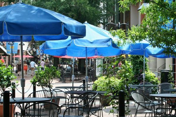Charlottesville, VA insurance agency, downtown outdoor cafe with iron tables and blue umbrellas on brick street.