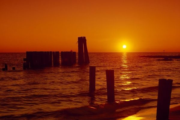 Eastern Shore of Virginia, old wharf pilings in shallow water with orange sunset in background.