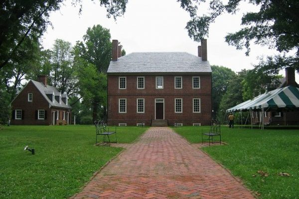 Fredericksburg, VA Kenmore_Plantation, two story brick home with slate roof, lush green lawn with tent ready for outdoor event.