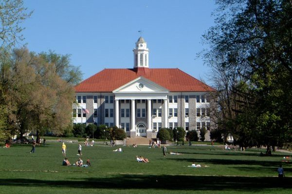 Harrisonburg, VA James Madison University large grey and white stone building with red terracotta roof before lush green lawn with students strewn about in various forms of repose or play.