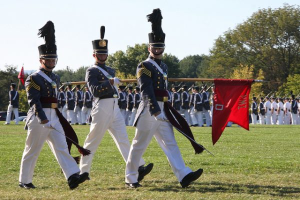 Lexington, VA Virginia Military Institute, parade on green field, three cadets in uniform of white pants and blue-gray felted wool jackets pass in review.