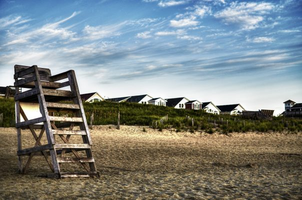 Outer Banks, NC empty beach with lifeguard stand in foreground, grass dunes and rooftops in background.